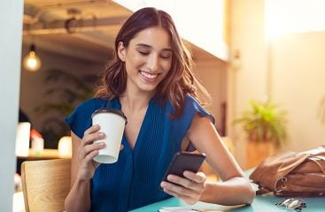 A women looking at her cell phone smiling drinking coffee